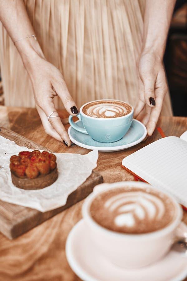 Filiżanki kawy latte i cukierki ciasto na drewnianym stole w kobiet rękach Delikatny romantyczny nastrój, dziewczyna jest ubranym zdjęcie royalty free