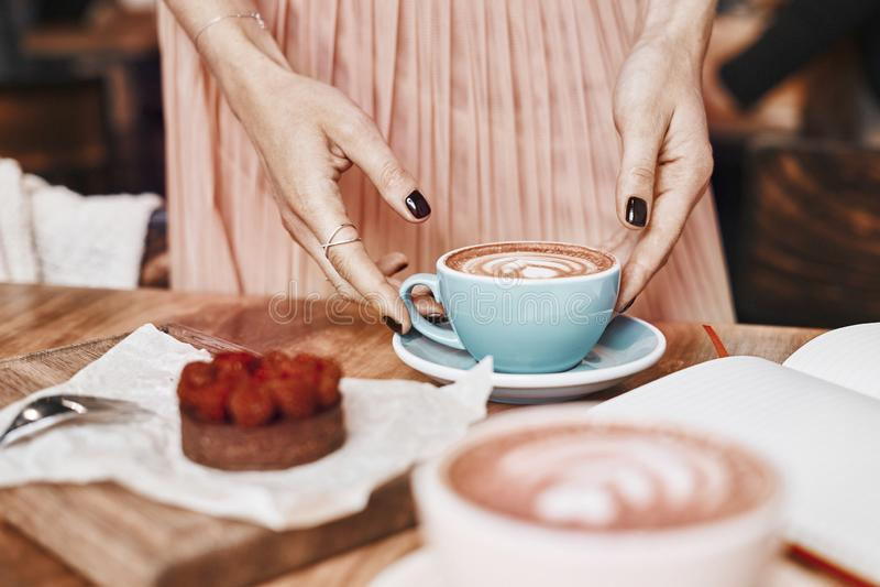 Filiżanki kawy latte i cukierki ciasto na drewnianym stole w kobiet rękach Delikatny romantyczny nastrój, dziewczyna jest ubranym zdjęcia stock