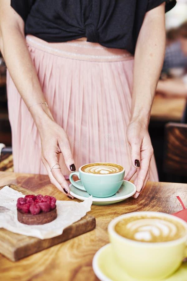 Filiżanki kawy latte i cukierki ciasto na drewnianym stole w kobiet rękach Delikatny romantyczny nastrój, dziewczyna jest ubranym fotografia royalty free