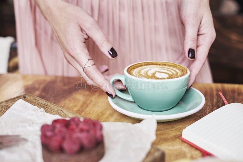 Filiżanki kawy latte i cukierki ciasto na drewnianym stole w kobiet rękach Delikatny romantyczny nastrój, dziewczyna jest ubranym zdjęcia royalty free