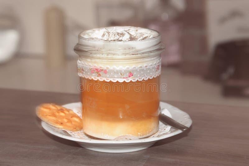 Filiżanki kawy latte macchiato z śmietanką, cynamonu proszkiem i tortem, zdjęcia stock