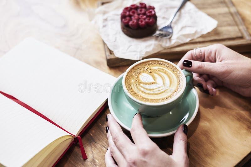 Filiżanki kawy latte na drewnianym stole lub tło w kobiet rękach od above Mieć lunch w kawiarni fotografia stock