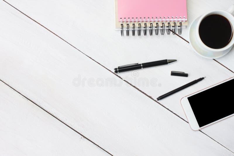 Filiżanki smartphone i pióro, notatnik na białym drewnianym biurku i obrazy royalty free