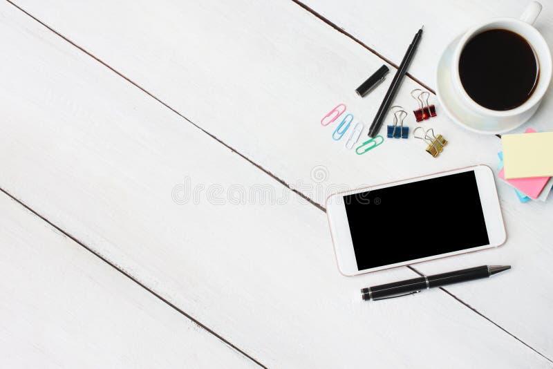 Filiżanki smartphone i pióro, notatnik na białym drewnianym biurku i zdjęcie stock