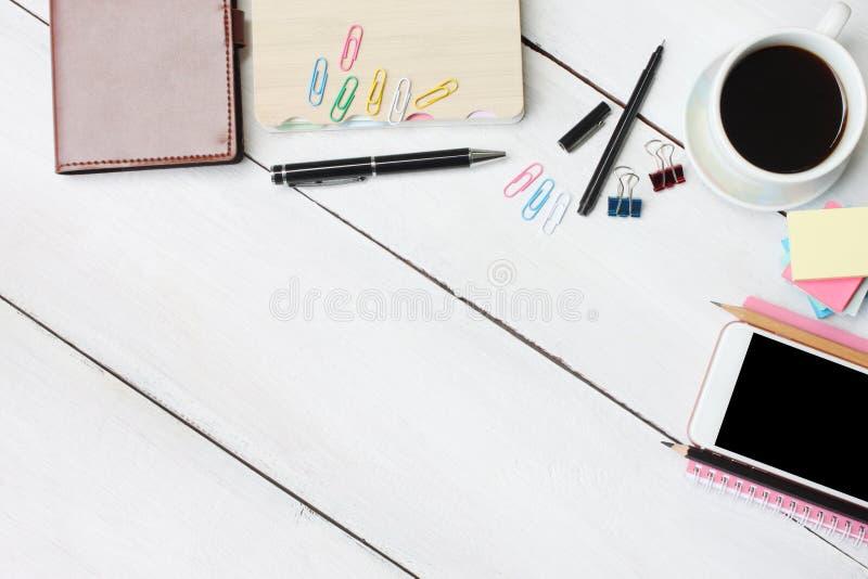 Filiżanki smartphone i pióro, notatnik na białym drewnianym biurku i fotografia royalty free