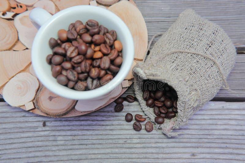 fili?anka groszkuje biel Piec kawowe fasole w prostackiej wyplatającej torbie fotografia royalty free