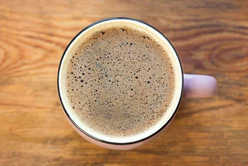 Fili?anka kawy na drewnianym tle Piękna piana, różowy ceramiczny kubek, elegancki tonowanie, kopii przestrzeń zdjęcie stock
