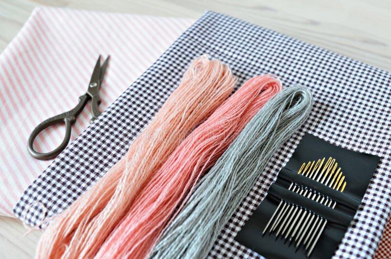 Fili pastelli del ricamo della lana, aghi, tessuto di cotone e retro forbici fotografia stock