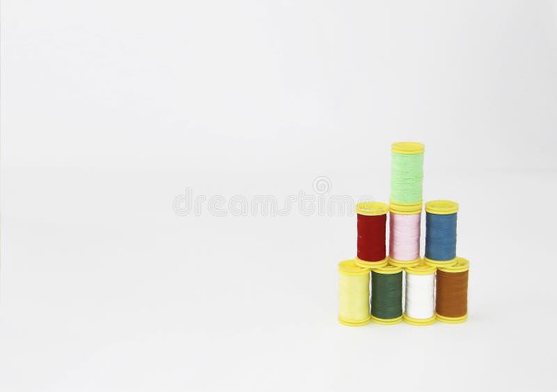 Fili variopinti per il cucito o ricamo su un fondo bianco immagini stock