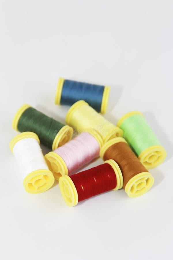 Fili variopinti per il cucito o ricamo su un fondo bianco immagine stock