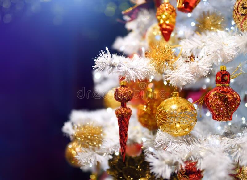 Filial av den vita konstgjorda julgranen som dekoreras med guld- och röda bollar på en blå bakgrund close upp royaltyfri fotografi