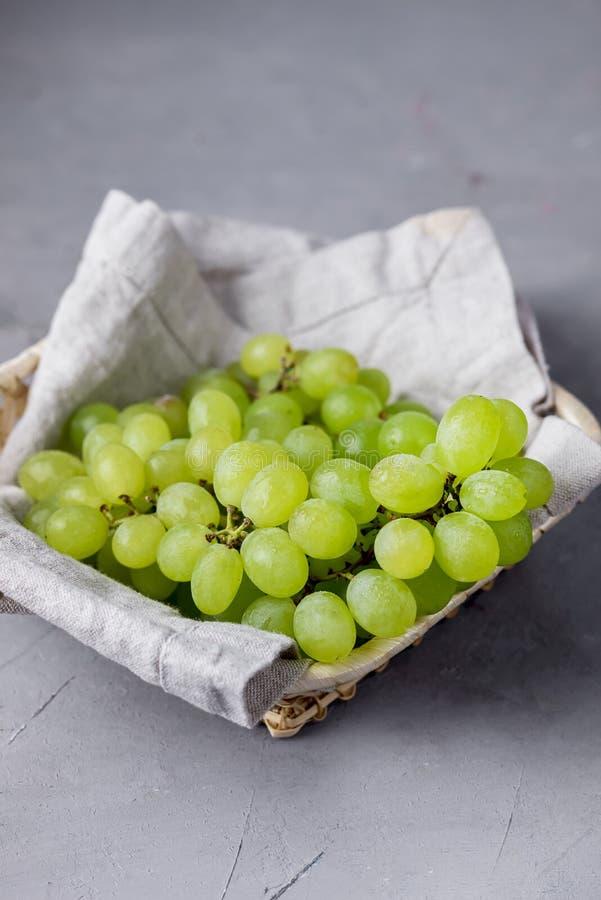 Filial av gröna druvor i korg på den Grey Background Tasty Summer Fruits lodlinjen arkivfoto