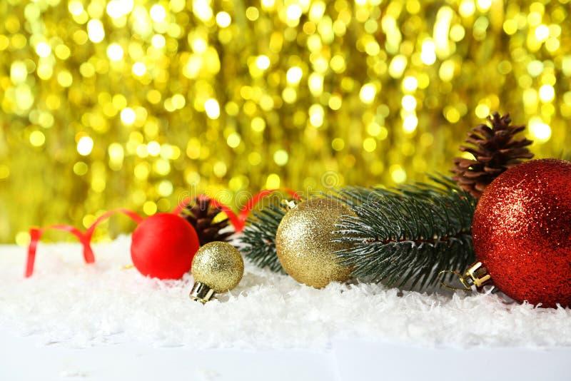 Filial av julgranen med bollar på snö, slut upp royaltyfri bild