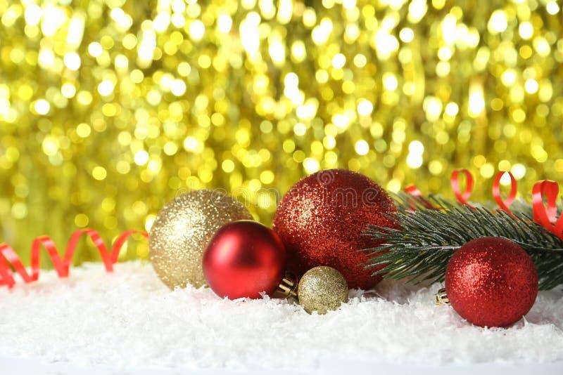 Filial av julgranen med bollar på snö, slut upp arkivfoton