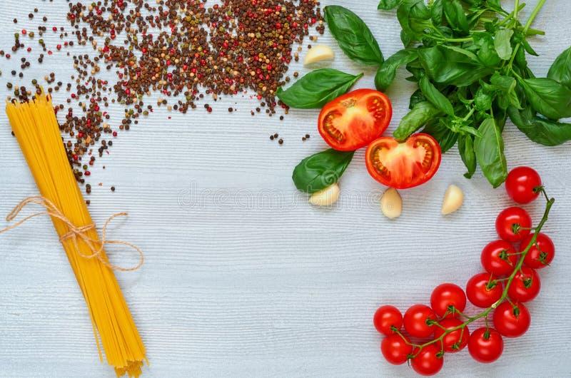 Filial av körsbärsröda tomater, basilika, vitlök, olik peppar och okokt pasta på den gråa bakgrunden Bästa sikt med kopieringsutr arkivfoton