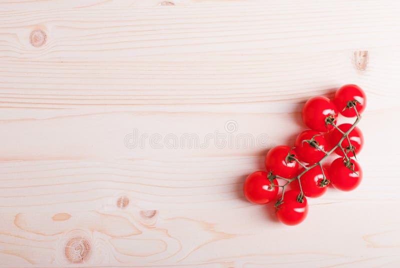 Filial av körsbärsröda tomater på en ljus träbästa sikt för tabell på th royaltyfria bilder