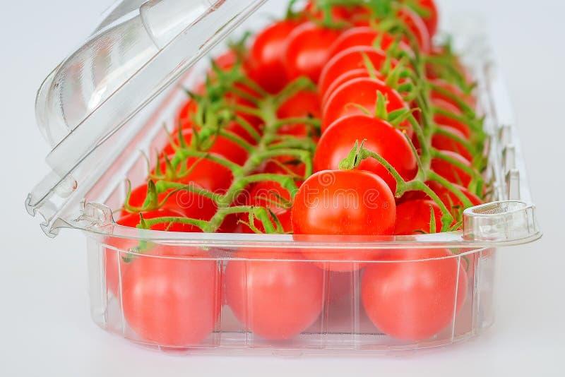 Filial av mogna röda körsbärsröda tomater i en genomskinlig plast- packe på en vit bakgrund Grönsaker, vegetarian och sunt royaltyfri foto