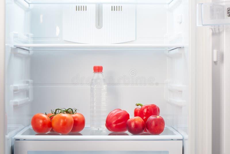 Filial av röda tomater, två röda peppar, två två-färgade orange och röda persikor och en flaska av vatten på hylla av den öppna t fotografering för bildbyråer