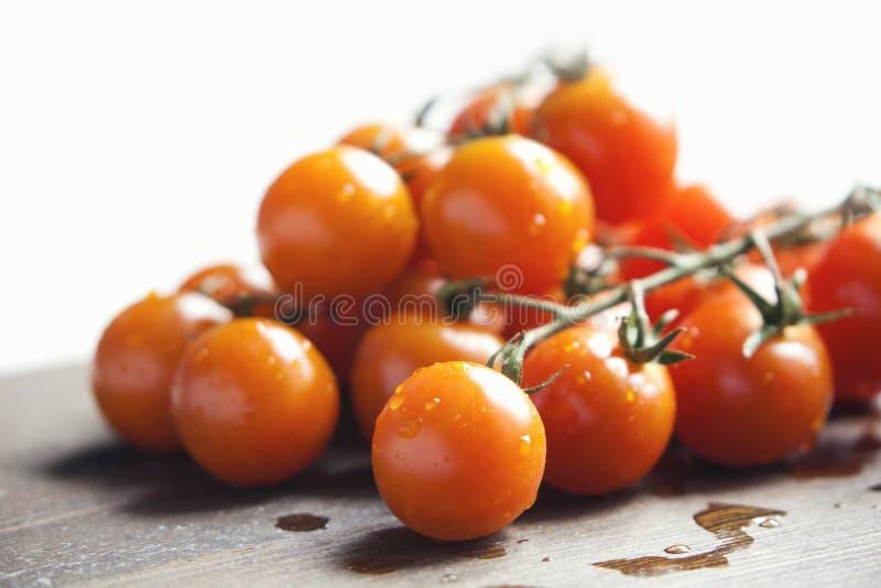 Filial för körsbärsröda tomater på en skärbräda arkivfoto