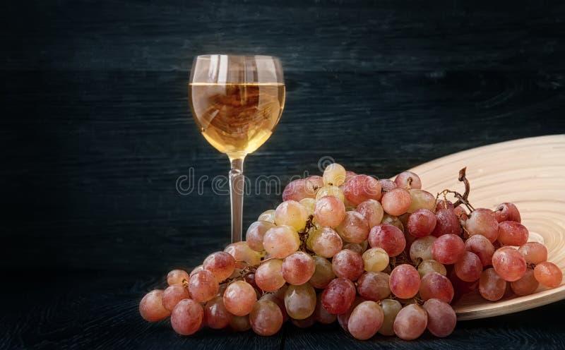 Filialen av druvor med ett exponeringsglas av vin arkivfoton