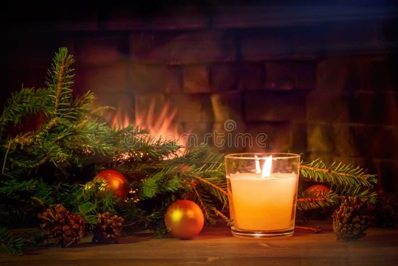 Filialer av en julgran, garneringar, en stearinljus på en trätabell framme av spisen Nytt ?r eller jul arkivfoton