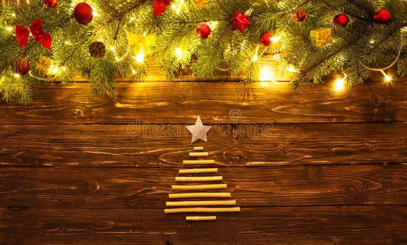 Filialer för julgranträd med leksaker på trätabellen Julbakgrund med granträdet och garnering med julgranen för arkivbilder