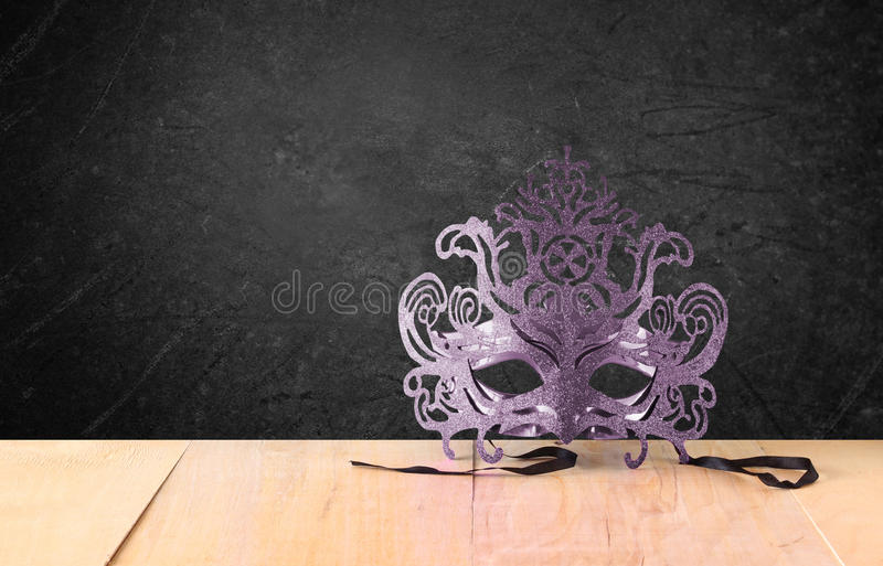 Filigree Mysterious Venetian masquerade mask on wooden table and texture black background.  royalty free stock image