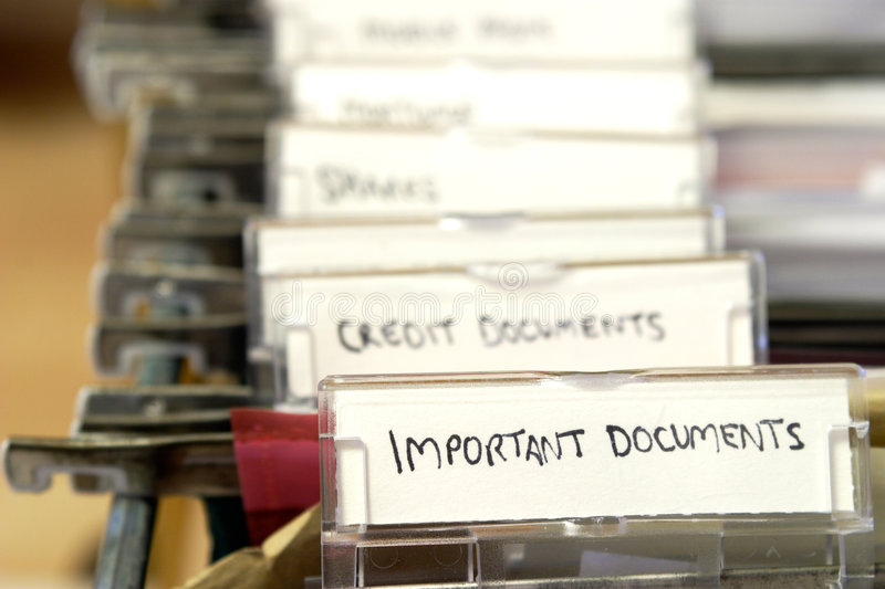 Filing. Detail of a filing cabinet with tabs labelled for important documents, credit documents, etc stock images