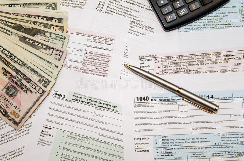 Filing federal taxes for refund - tax form 1040. Calculator, pen and dollar stock images