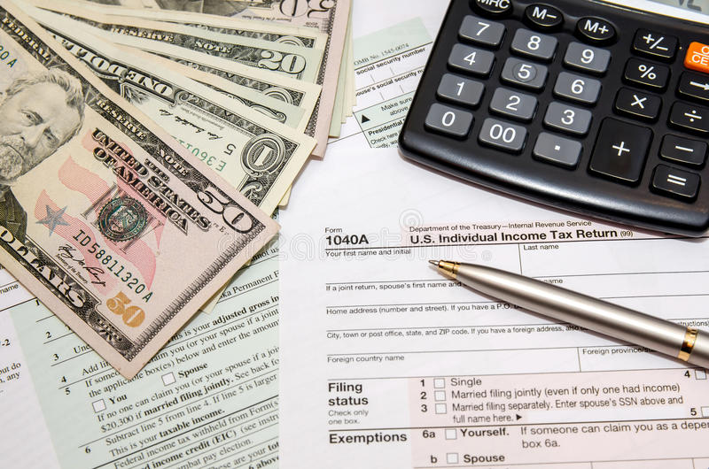 Filing federal taxes for refund - tax form 1040. Calculator, pen and dollar royalty free stock photo