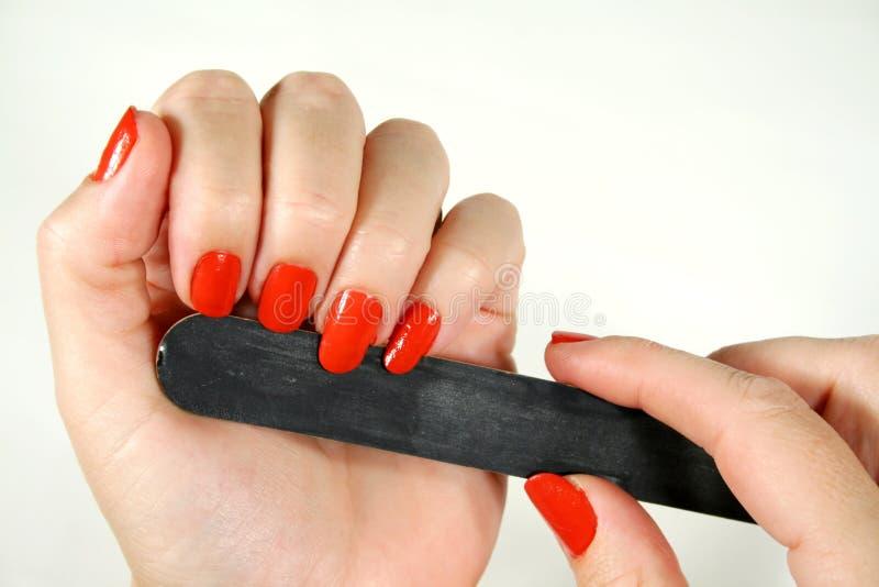 Filing Fingernails. Female filing her fingernails with an emery board stock image