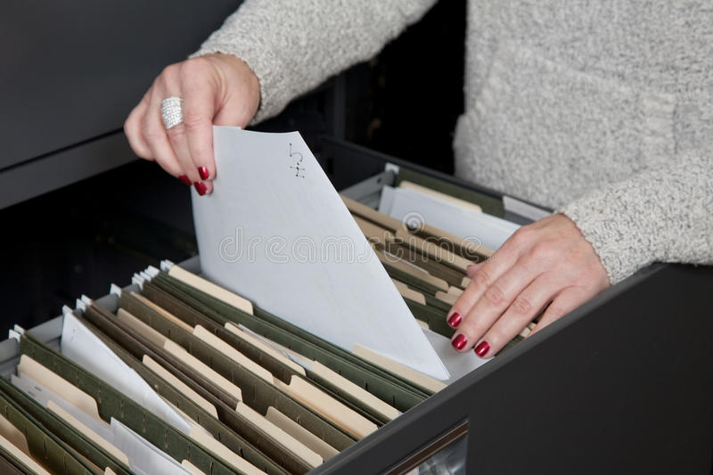 Filing Paperwork. Female organizes paperwork into an office filing cabinet royalty free stock photo