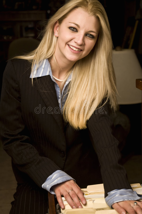 Filing paperwork. Young business woman searching through file cabinet stock image
