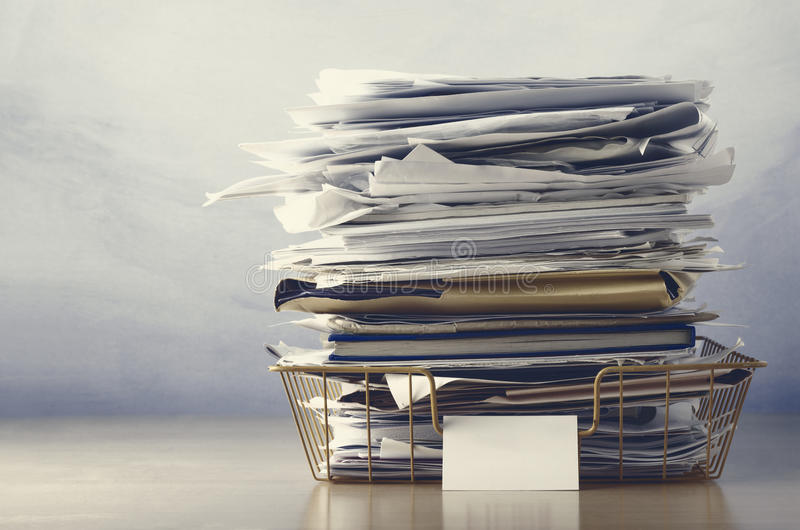 Filing Tray Piled High with Documents in Drab Hues. An old wireframe filing tray, piled high with documents and folders, on a light wood veneer desk. Drab hues royalty free stock photography