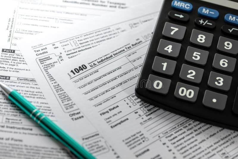 Filing u.s. individual income tax return form 1040. Individual income tax return form 1040 and calculator stock photos