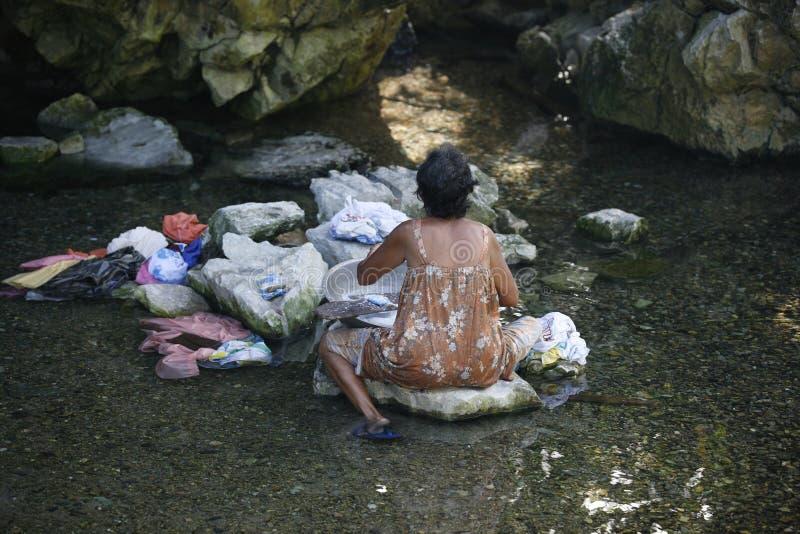 Filipińska starsza kobieta myje ubrania w rzece Filipiny Katiklan obraz stock