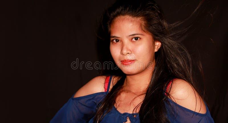 Filipina bastante joven que mira a través de la cámara imagen de archivo libre de regalías