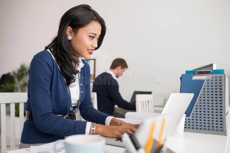 Filipina business lady. Beautiful Filipina business lady working on laptop in the office royalty free stock photos