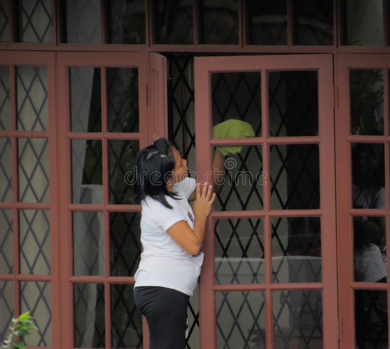 Filipina Maid Cleaning Window. Domestic Filipina maid wiping window in a Malaysian home royalty free stock photo