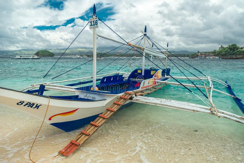 Filipino boats in the azure sea in Boracay at clouds day, Philippines. August 2016. Filipino boats in the azure sea in Boracay at clouds day, Philippines royalty free stock photography
