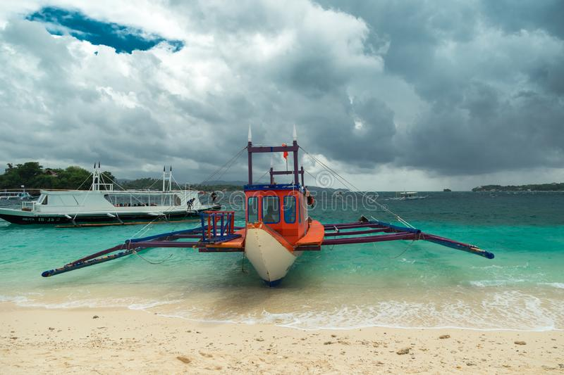 Filipino boats in the azure sea in Boracay at clouds day, Philippines. August 2016. Filipino boats in the azure sea in Boracay at clouds day, Philippines stock photo