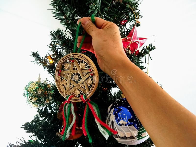 Filipino Christmas. Filipino decorating Christmas tree with traditional parol ornament stock photo
