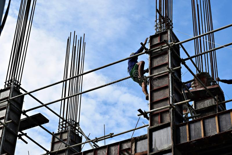 Filipino construction steel-man climbing down using scaffolding pipes on high-rise building. San Pablo City, Laguna, Philippines - June 20, 2018: Filipino royalty free stock images