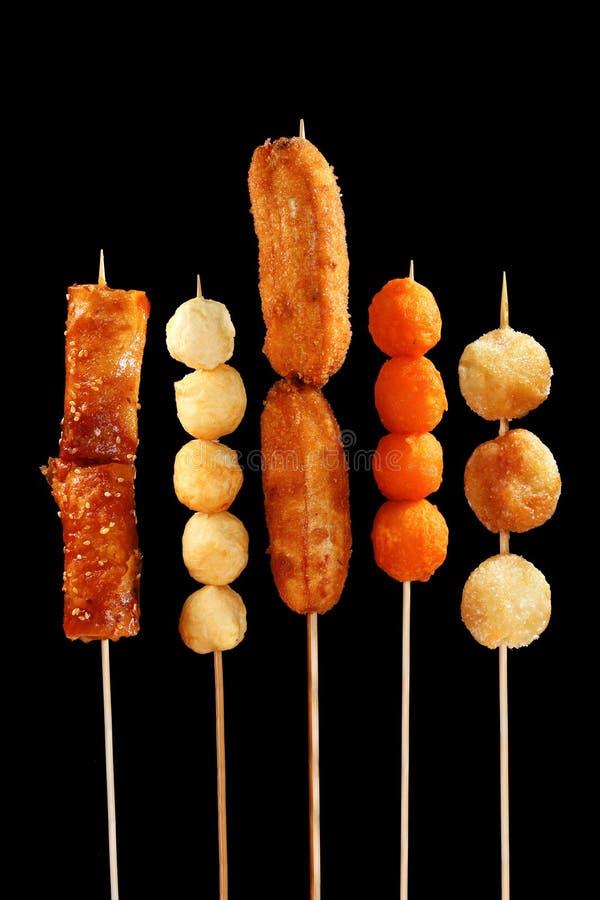 Filipino street food on sticks. On black background royalty free stock photos