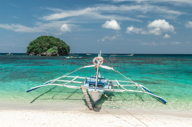 Filipino tourist boat in the emerald azure sea on small island background. Boracay, Philippines - January 2018 royalty free stock image