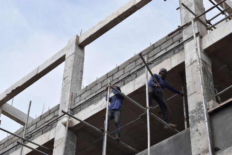 Filippinska byggnadsarbetare som installerar metall, leda i rör ställningar på höghus utan den skyddande dräkten royaltyfria bilder