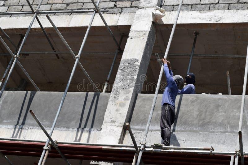 Filippinska byggnadsarbetare som installerar metall, leda i rör ställningar på höghus utan den skyddande dräkten fotografering för bildbyråer