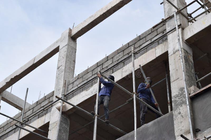 Filippinska byggnadsarbetare som installerar metall, leda i rör ställningar på höghus utan den skyddande dräkten arkivfoton