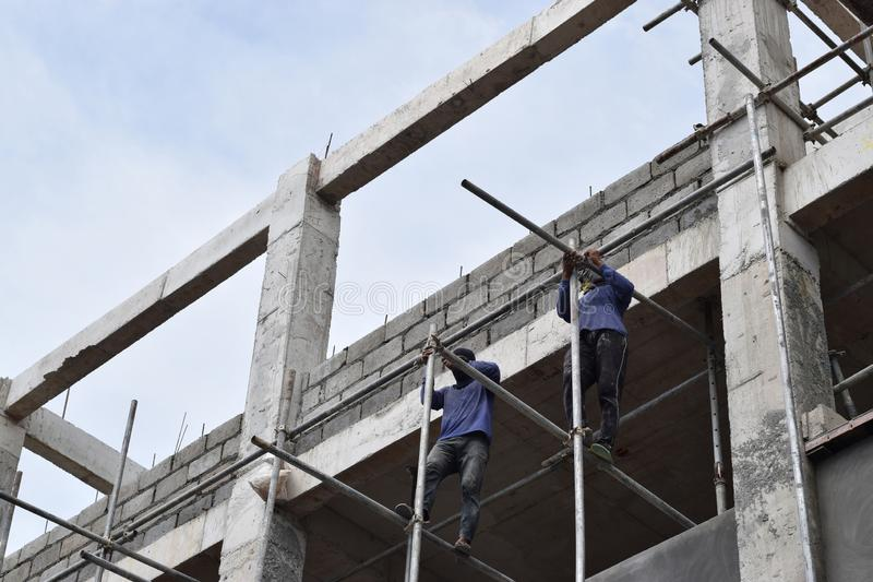 Filippinska byggnadsarbetare som installerar metall, leda i rör ställningar på höghus utan den skyddande dräkten royaltyfri fotografi