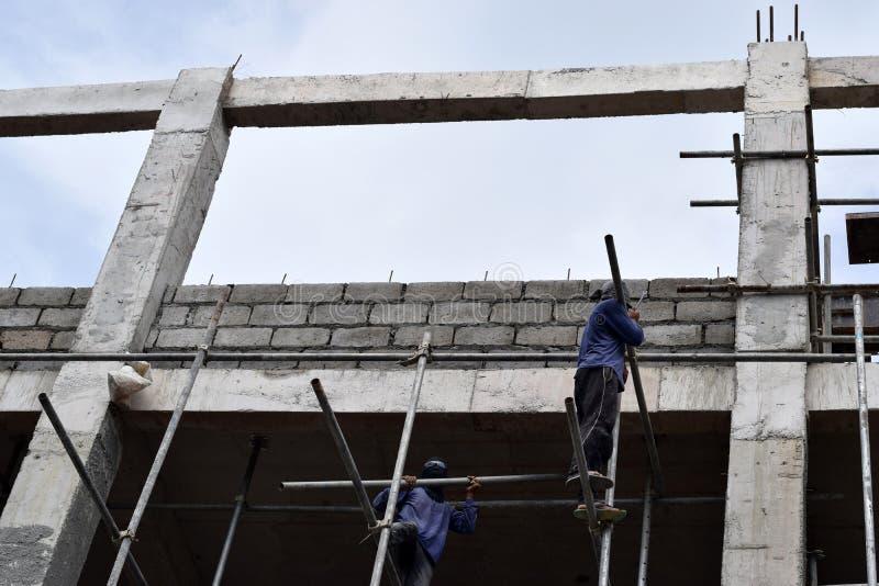 Filippinska byggnadsarbetare som installerar metall, leda i rör ställningar på höghus utan den skyddande dräkten arkivbilder